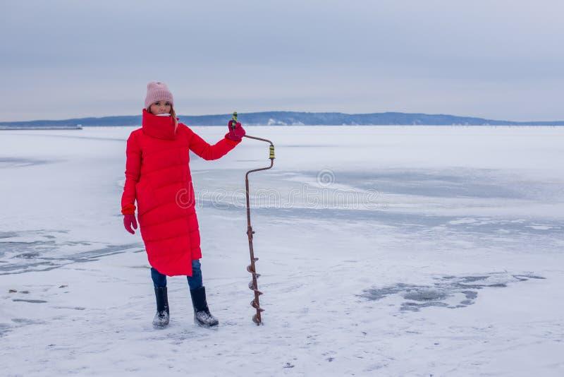 Nette schöne junge Frau mit Eisbohrständern auf gefrorenem Fluss und bereitet sich für die Fischerei vor lizenzfreie stockbilder