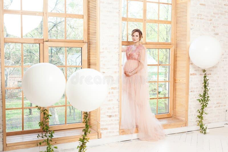 Nette schöne schwangere junge Frau in der rosa Kleiderstellung auf Fensterbrett und im Halten mit Liebe ihres Bauches lizenzfreies stockfoto