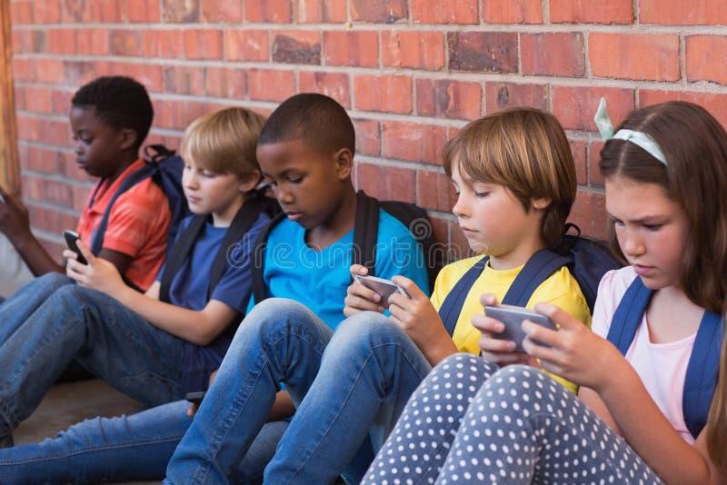 Nette Schüler, die Handy verwenden stockfoto