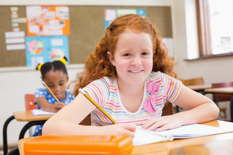 Nette Schüler, die am Schreibtisch in Klassenzimmer schreiben lizenzfreies stockfoto