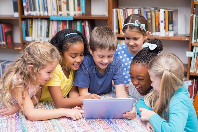 Nette Schüler, die Tablette in der Bibliothek betrachten stockbilder
