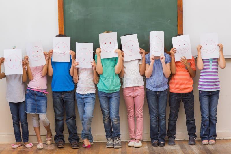 Nette Schüler mit lustigen Gesichtern im Klassenzimmer lizenzfreies stockbild