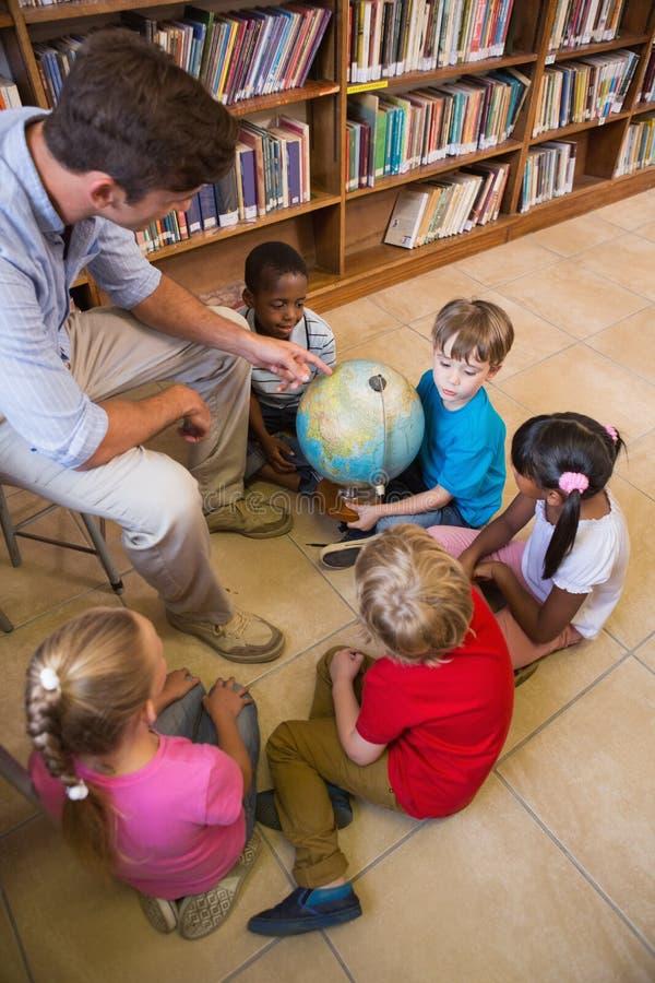 Nette Schüler und Lehrer, die Kugel in der Bibliothek betrachtet lizenzfreie stockfotografie