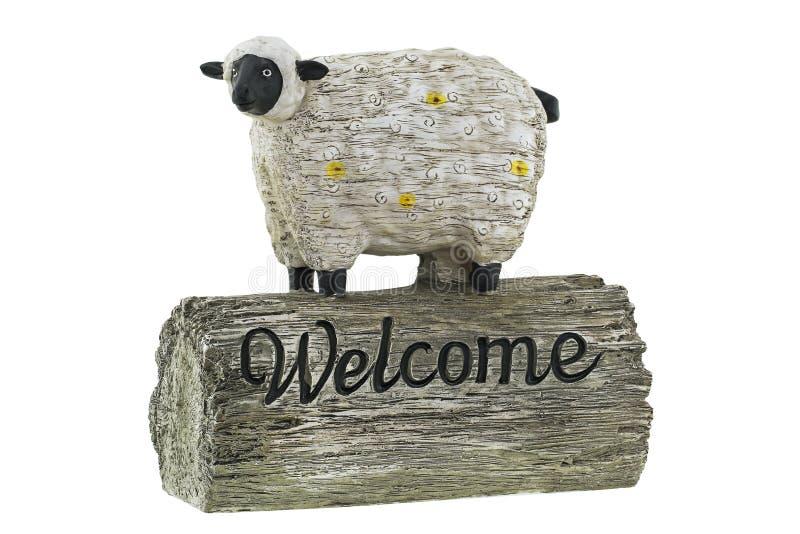Nette Schaffigürchen mit Wortwillkommen auf einem hölzernen Klotz stockfotografie