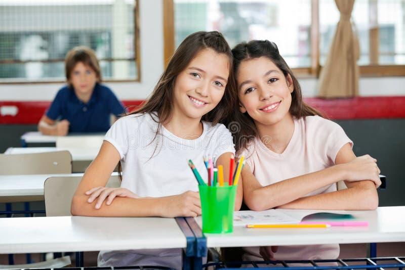 Nette Schulmädchen, die zusammen am Schreibtisch sitzen lizenzfreies stockfoto