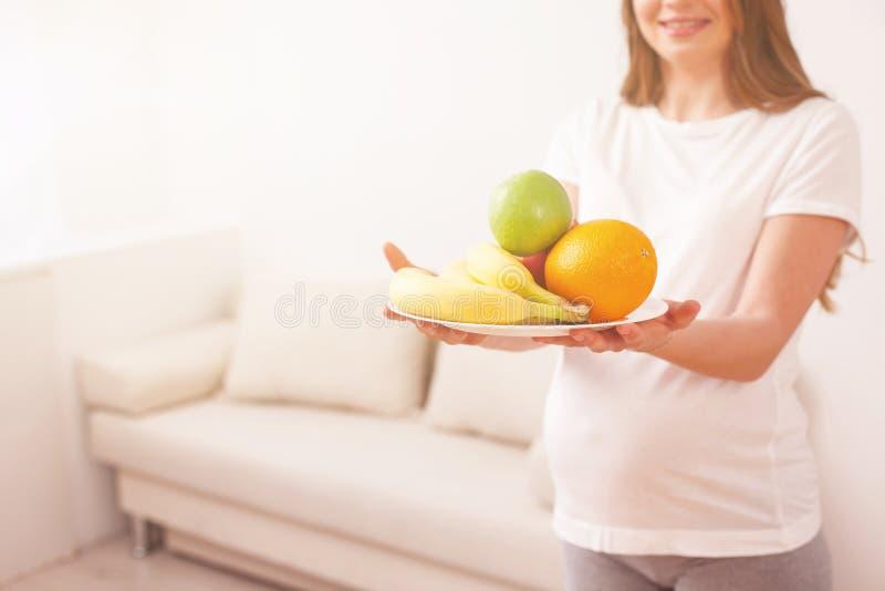 Nette schwangere Frau ist von ihrer Gesundheit mitfühlend stockbilder