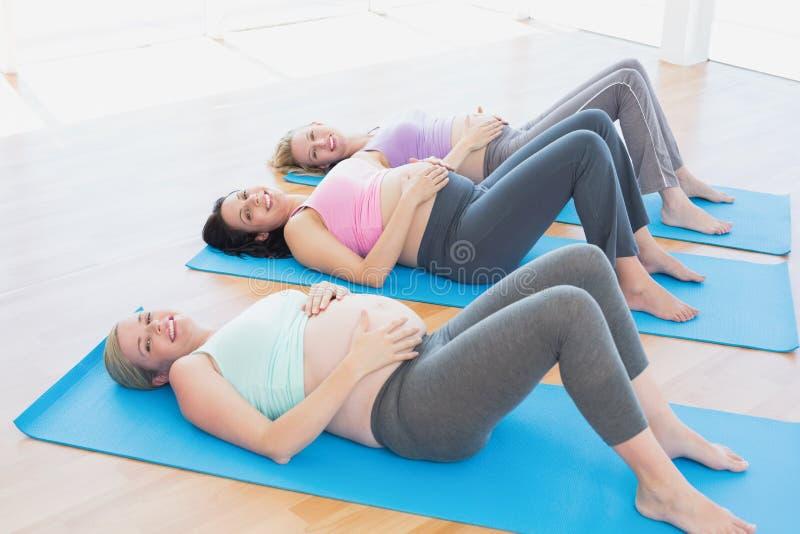 Nette schwangere Frauen im Yoga klassifizieren das Lügen auf Matten lizenzfreie stockfotos
