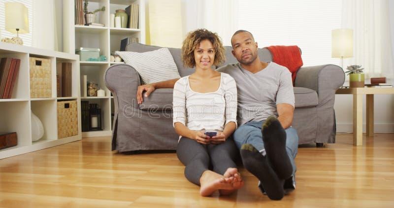 Nette schwarze Paare, die auf Boden im Wohnzimmer sitzen stockbilder