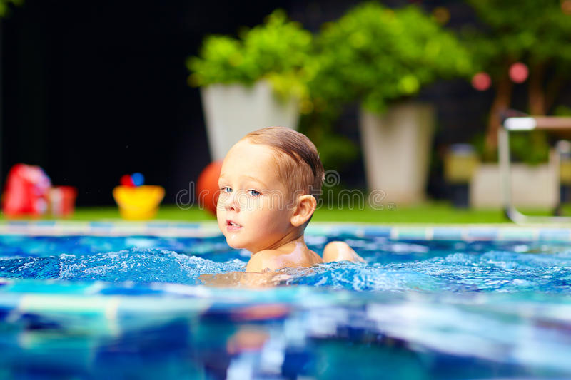 Nette Schwimmen des kleinen Jungen auf Pool lizenzfreie stockfotografie