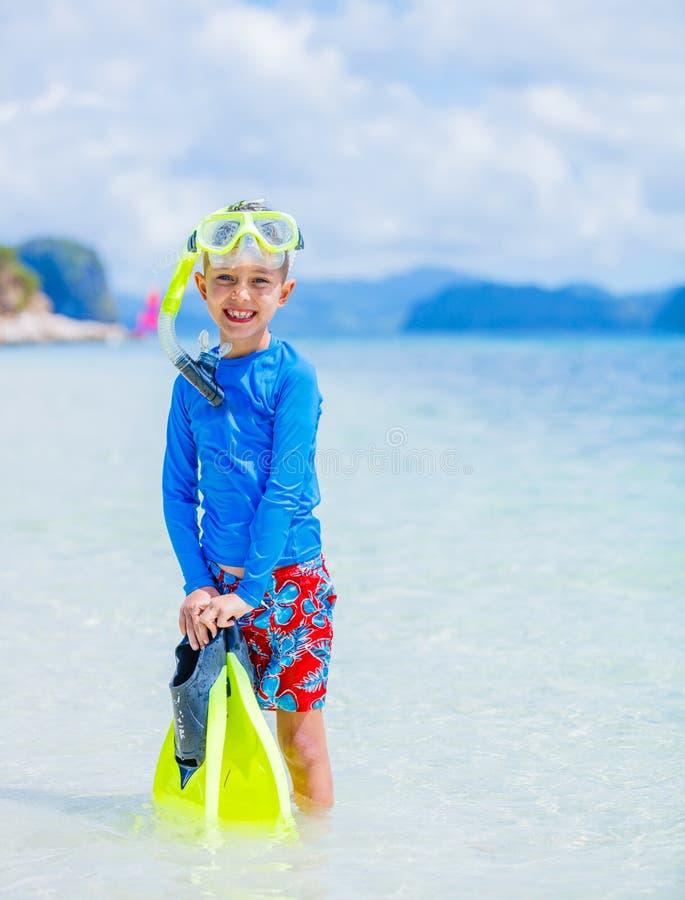 Nette Schwimmen des kleinen Jungen auf tropischem Strand stockfoto