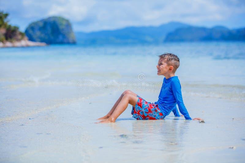 Nette Schwimmen des kleinen Jungen auf tropischem Strand lizenzfreies stockbild