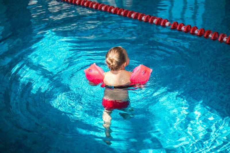 Nette Schwimmen des kleinen M?dchens im Pool stockbild