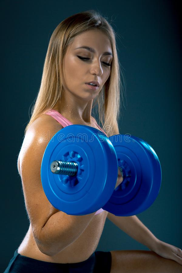 Nette sexy Frau, die Training mit Dummköpfen über dunklem Hintergrund tut stockbilder