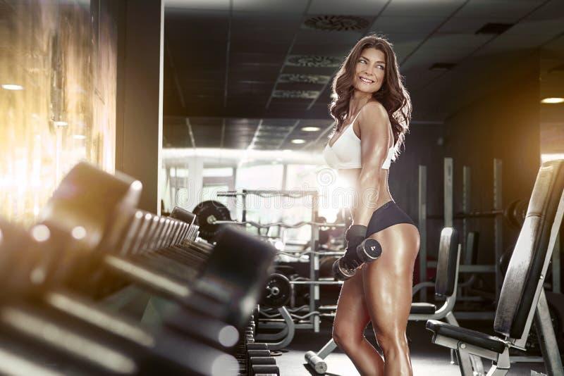 Nette sexy Frau, die Training mit Dummköpfen tut stockbild