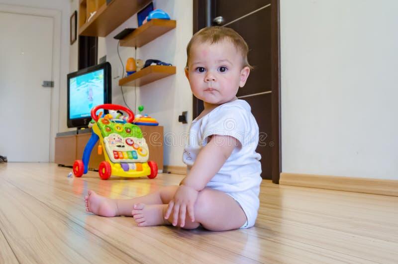 Nette sieben Monate alte Baby, die mit pädagogischen Spielwaren auf dem Boden spielen lizenzfreie stockbilder