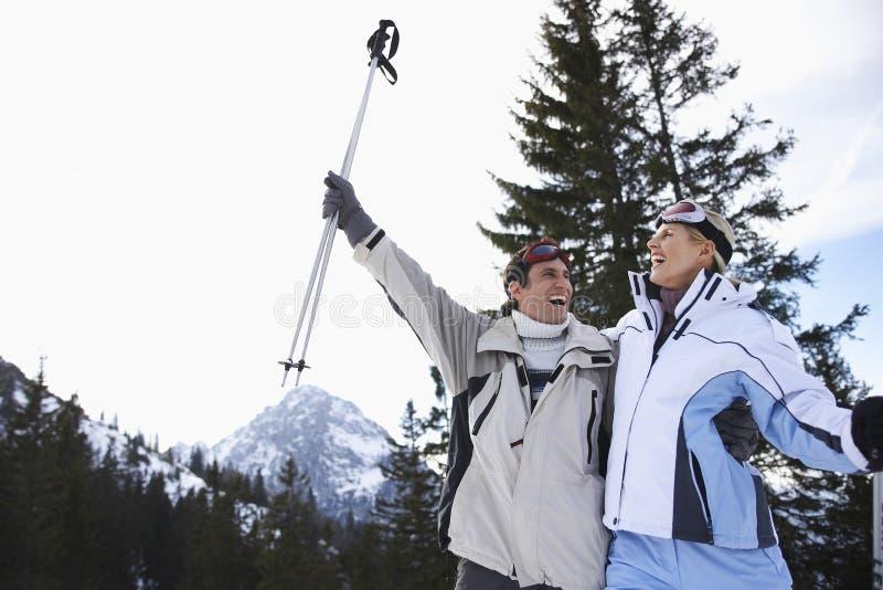 Nette Skifahren-Paare in der warmen Kleidung mit Skis lizenzfreie stockfotografie