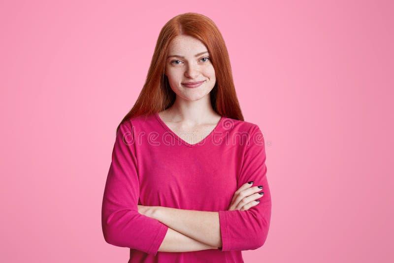 Nette sommersprossige Frau mit dem langen Ingwerhaar steht gekreuzte Hände, trägt rosa Strickjacke und freut sich, die Freunde zu stockfotografie