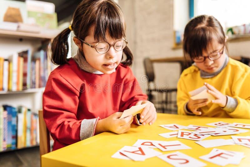 Nette sonnige Kinder, die beim Lernen von Buchstaben interessiert sich fühlen lizenzfreie stockfotos