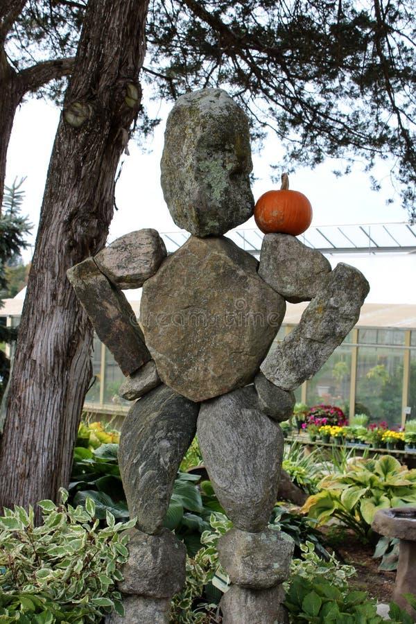 Nette Steinskulptur mit dem kleinen Kürbis balanciert auf der Schulter, gesehen an der populären Kindertagesstätte Connecticut, 2 stockbild
