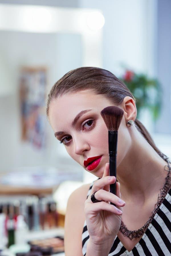 Nette Stellung der jungen Frau mit einer Pulverbürste stockfotografie