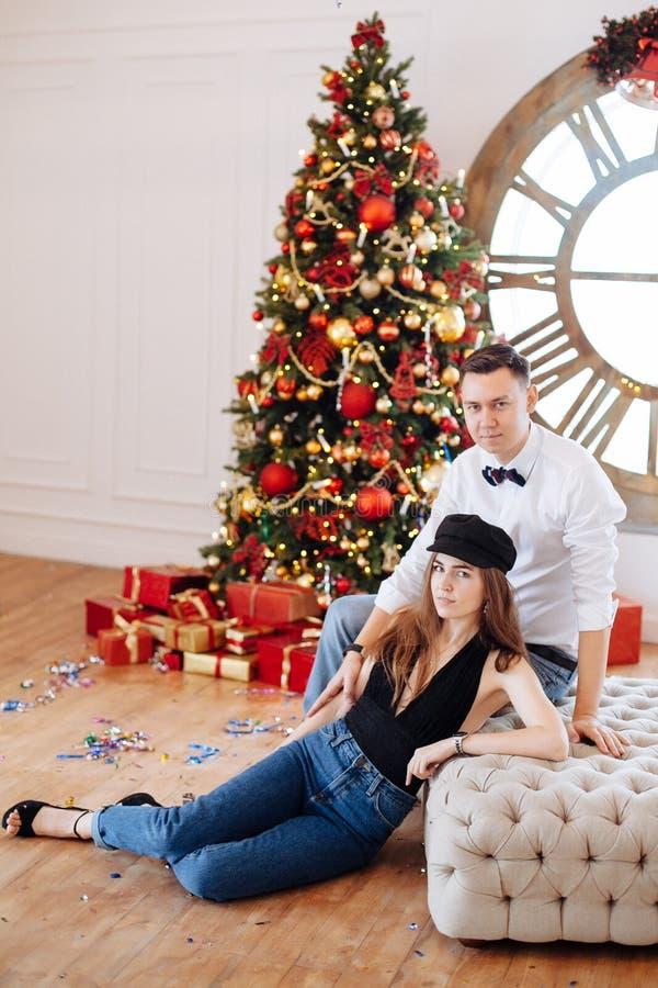 Nette stilvolle Paare, die nahe rotem Weihnachtsbaum sitzen lizenzfreie stockfotografie