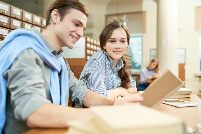 Nette Studenten, die neues Material in der Bibliothek lernen stockfoto