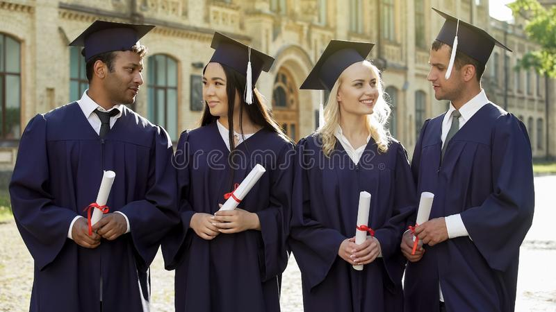 Nette Studenten im Aufbaustudium in den akademischen Insignien miteinander sprechend, Erfolg lizenzfreies stockfoto