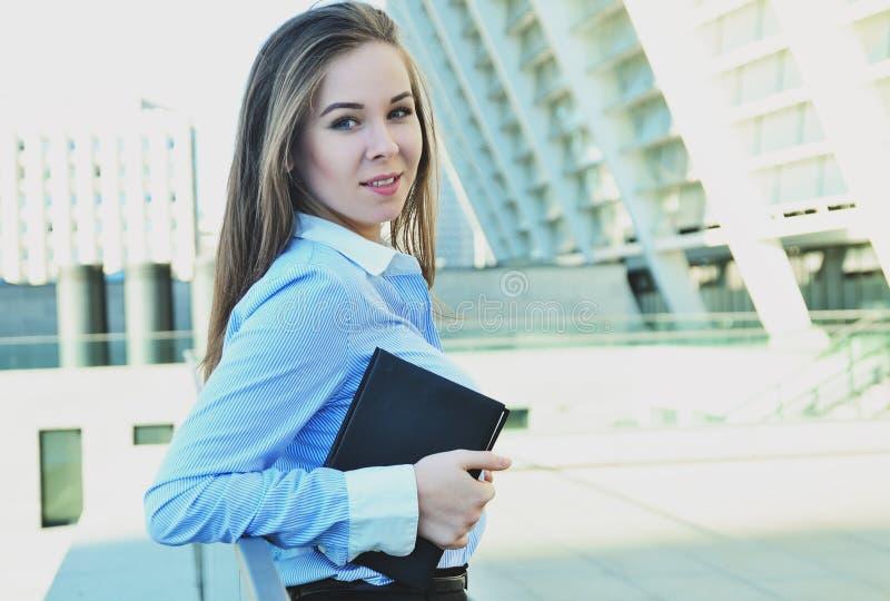 Nette Studentin in der schönen Bürokleidung, stehend nahe dem Geländer und halten ein schwarzes Notizbuch lizenzfreie stockfotografie