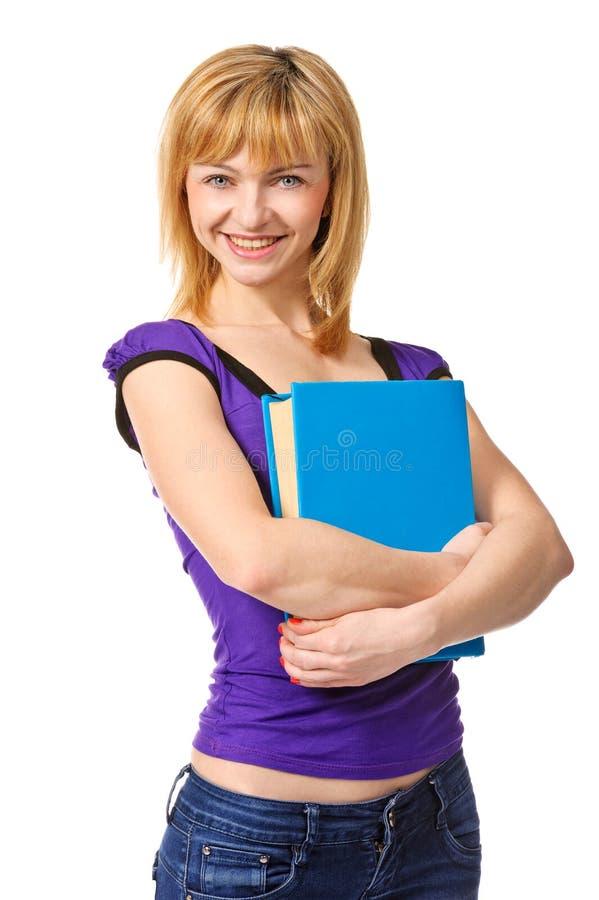 Nette Studentin, die Buch anhält, Kamera lächelt und betrachtet stockfoto