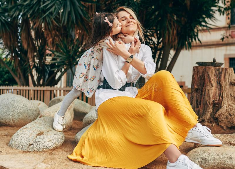 Nette Tochterumarmung ihre junge Mutter im gelben Rock, der auf dem Felsen im Park sitzt stockfotografie