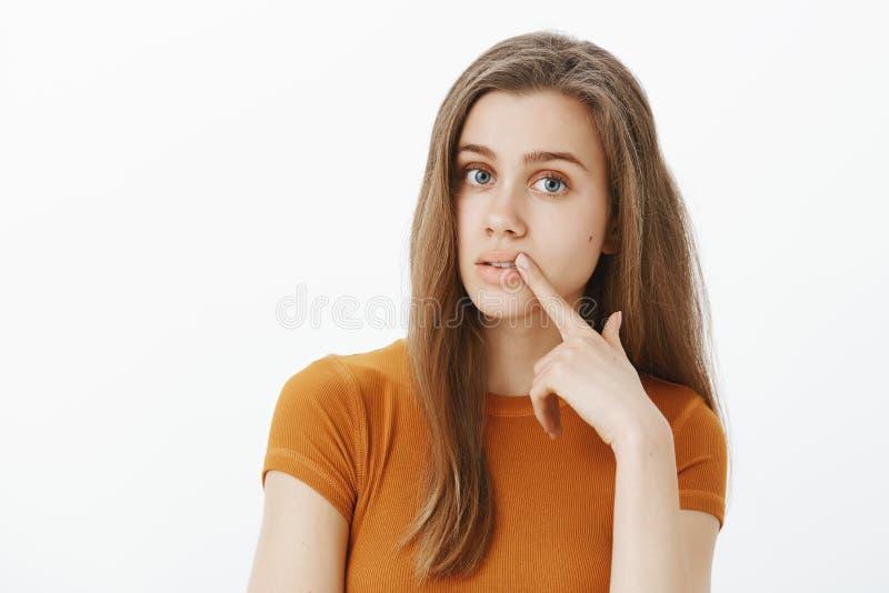 Nette träumerische weibliche Frau in der stilvollen Ausstattung, starrend Kamera und rührende Lippe mit dem Zeigefinger an und de lizenzfreie stockfotos