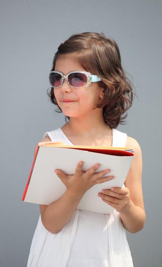 Nette tragende Sonnenbrillen und Lächeln des kleinen Mädchens stockfoto