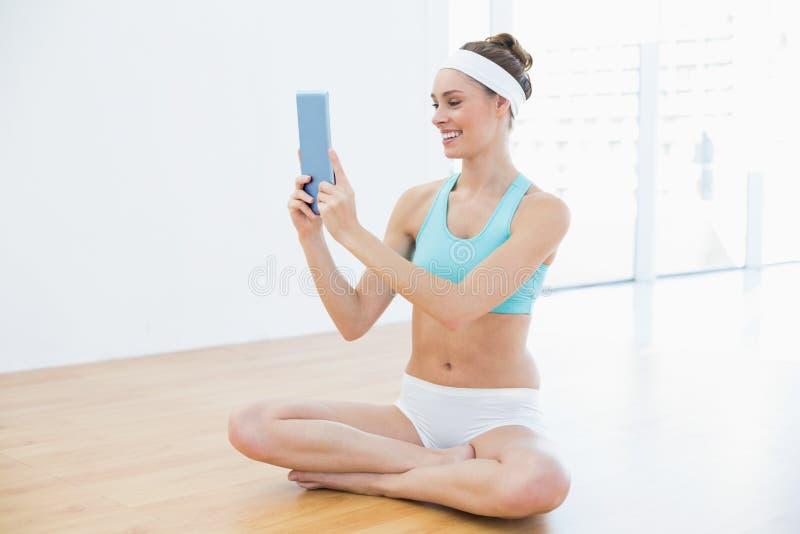 Nette tragende Sportkleidung der jungen Frau unter Verwendung ihrer Tablette stockfoto