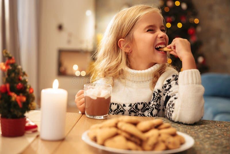 Nette trinkende Kakao des kleinen Mädchens und zu Hause essen Plätzchen lizenzfreies stockfoto