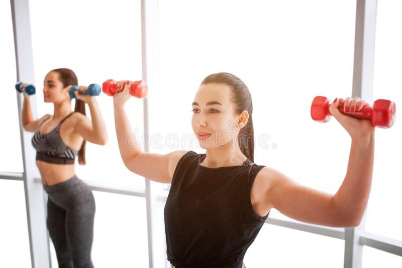Nette und überzeugte junge Frauen, die mit Dummköpfen am Fenster trainieren Asiatischer vorbildlicher Stand in der Front und im B stockfotografie