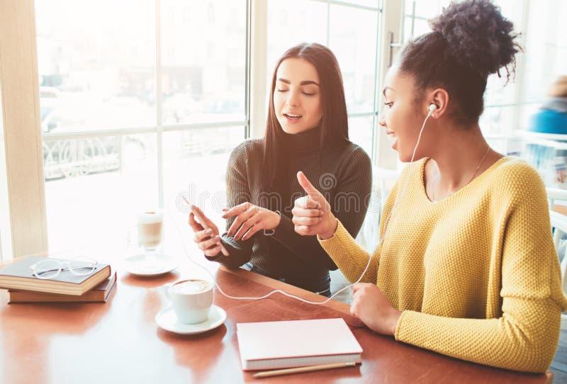 Nette und attraktive Mädchen sitzen nahe dem hellen Fenster im Café Ein Mädchen, das Musik während das andere hört lizenzfreie stockfotografie