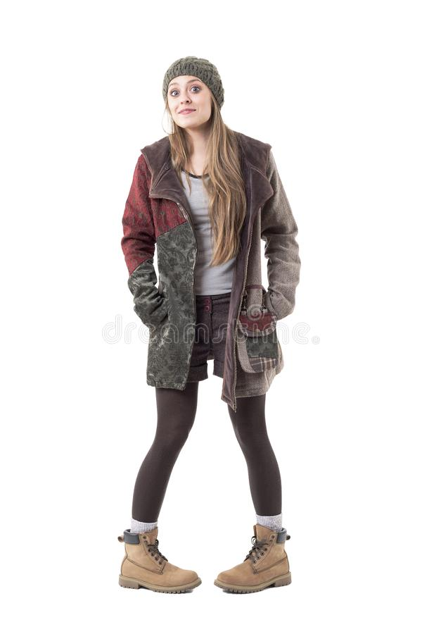 Nette unschuldige weibliche junge neugierige Frau in der Winterkleidung, die mit Taubenzehenlage aufwirft stockbild