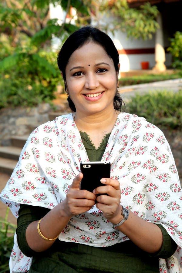 Nette Versenden von SMS-Nachrichten der jungen Frau stockfoto