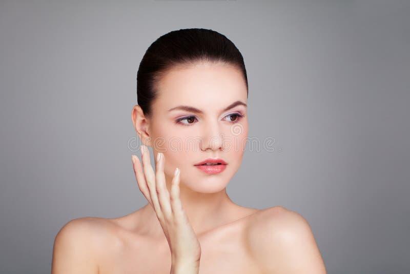 Nette vorbildliche Frau mit klarer Haut auf grauem Hintergrund lizenzfreie stockbilder