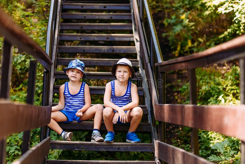 Nette Vorschülerkinder in den T-Shirts, in Turnschuhen und in Hüten, die auf den Schritten im Sommer sitzen stockbilder