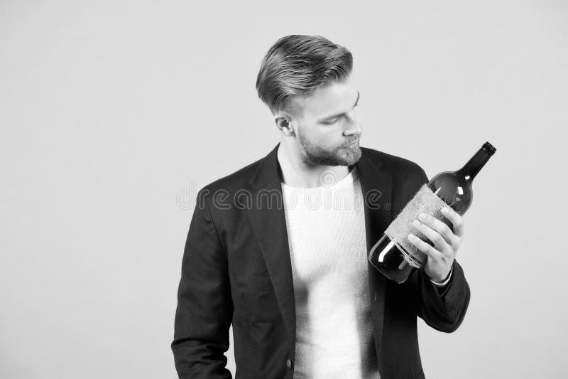 Nette Wahl Mann hält Flaschenalkoholgetränk Sozial- und kulturelle Aspekte des Trinkens Durchdachte Schätzungsflasche des Mannes stockbilder