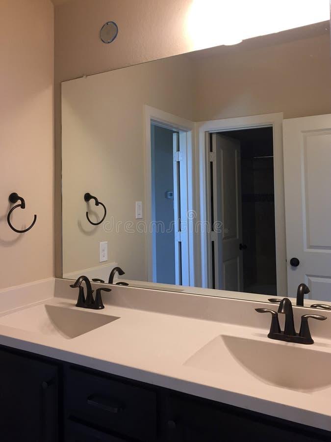 Nette Wannen des Badezimmers zwei und großer Spiegel auf der Wand lizenzfreies stockbild