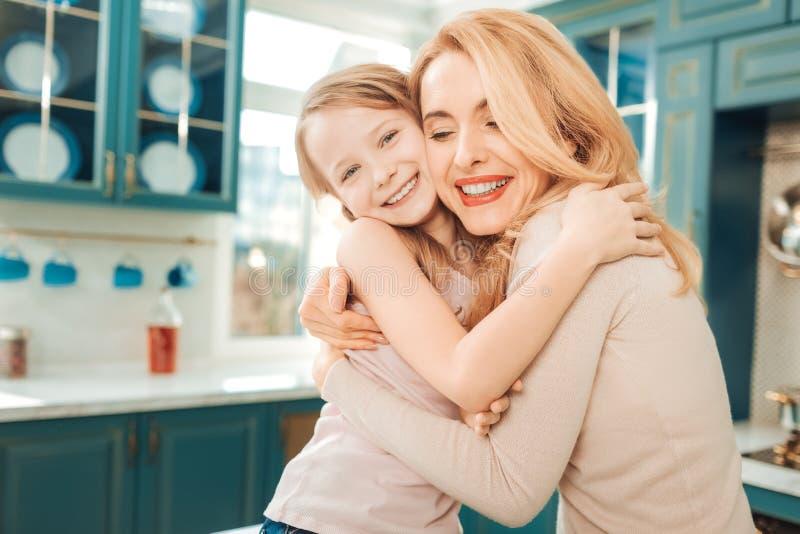 Nette weibliche Person, die ihre kleine Tochter umarmt stockfoto