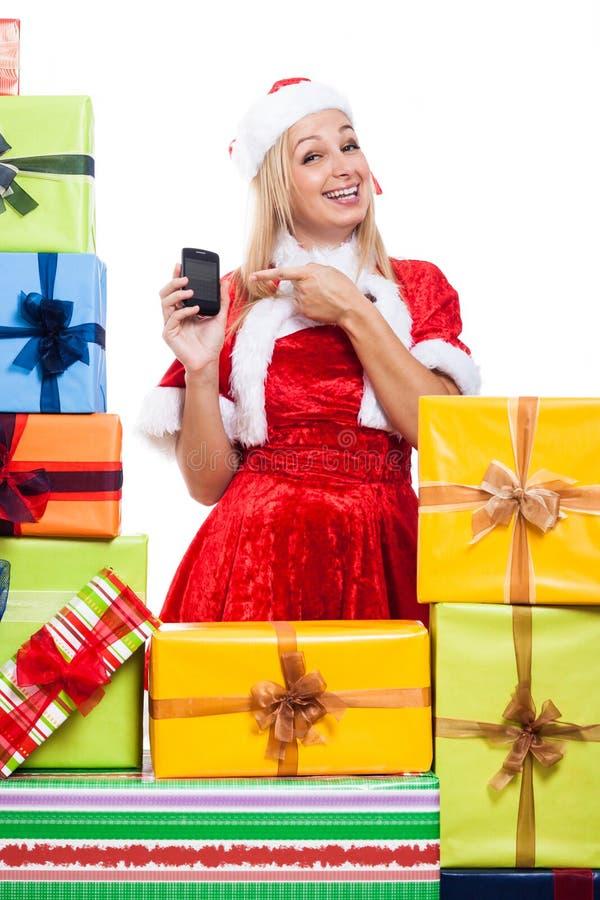 Nette Weihnachtsfrau mit Telefon und Geschenken lizenzfreies stockbild