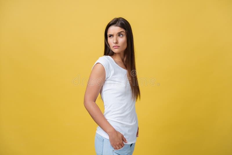 Nette Winks und Blick des jungen Mädchens weg an der Kamera in einem Studio auf einem gelben Hintergrund stockfotos