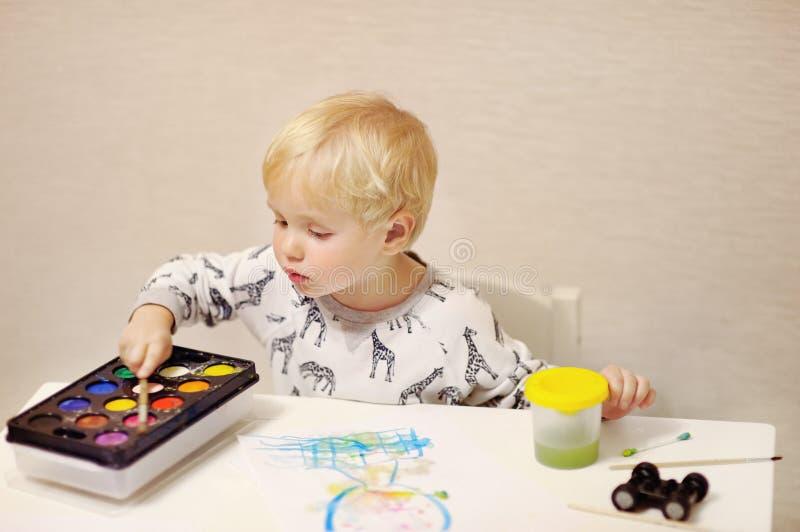 Nette Zeichnung des kleinen Jungen mit bunten Farben zu Hause stockbild