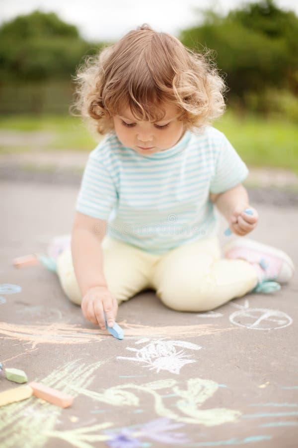 Nette Zeichnung des kleinen Mädchens mit Farbkreide stockfoto