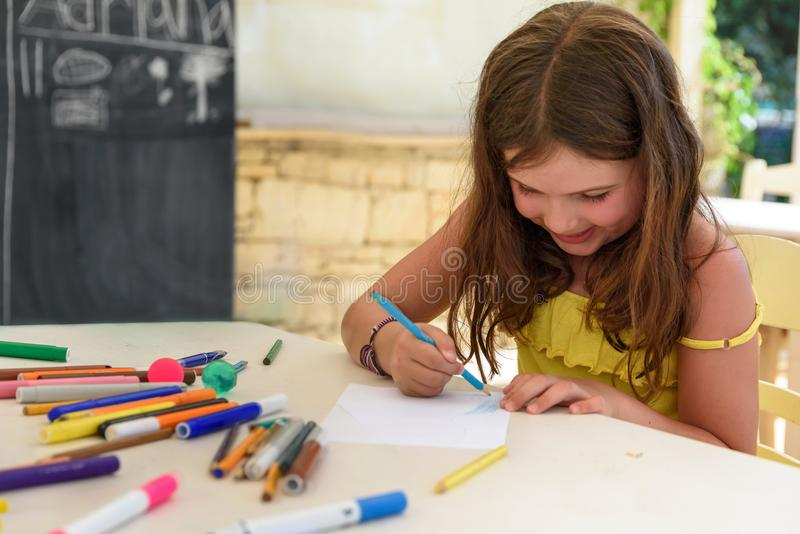 Nette Zeichnung und Malerei des kleinen Mädchens am Kindergarten Kreativer Tätigkeitskinderverein lizenzfreie stockbilder
