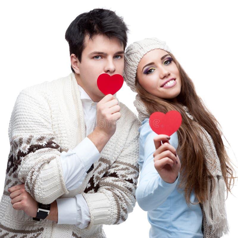 Nette zufällige junge Paare, die rote Herzen halten lizenzfreie stockfotos