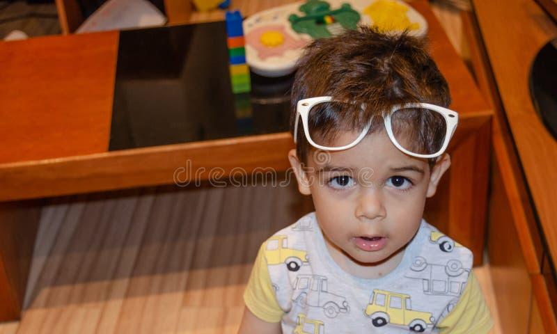 Nette zwei Jahre alte Junge, die mit wei?en Gl?sern spielen und lustige Gesichter machen stockfotografie